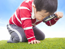 A boy exploring nature with magnifying glass Royalty Free Stock Photography