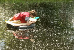 Boy Exploring Pond. A young boy floats on a homemade raft out on a pond in springtime.  He searches the water for frogs, bugs, and whatever he can see.  Having Royalty Free Stock Images