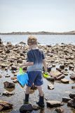 Boy exploring tide pools on New Hampshire coast. Curious Four year old boy exploring rocky tide pools on the coast of New Hampshire looking for sea life stock images