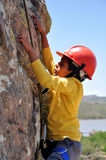Boy Extreme sports. Boy climbing rocks, wearing a harness and a hard hat Stock Image