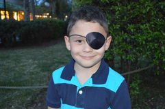 Boy with an eye patch. Little boy wearing a pirate eye patch, smiling Stock Photos