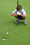 Boy Eyeballs Gimme Golf Putt. Young boy studies an easy gimme putt on a golf green Royalty Free Stock Photos