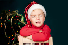 Boy with eyes closed in cap of Santa Claus Stock Photo