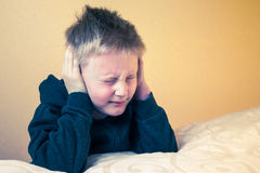Boy with eyes closed covering ears with hands Royalty Free Stock Photography