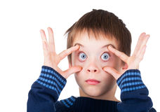 Boy with eyes wide open. Child wearing blue sweater making funny face holding his eyes wide open on white background Stock Images