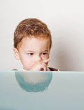 Boy face behind glass table Stock Image
