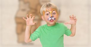 Boy with facepaint growling against blurry brown map. Digital composite of Boy with facepaint growling against blurry brown map Royalty Free Stock Photography