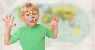 Boy with facepaint growling against blurry map. Digital composite of Boy with facepaint growling against blurry map Stock Photo
