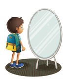 A boy facing the mirror Stock Image