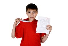 Boy with failing grade. A young boy is worried about a failing grade on his homework. Isolated on white Royalty Free Stock Images