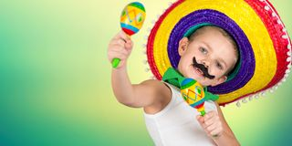 Mexican party.Boy with a fake mustache in a sombrero playing the maracas. Boy with a fake mustache in a sombrero playing the maracas.Mexican party stock photo
