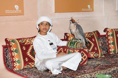 Boy with Falcon in Abu Dhabi International Hunting and Equestrian Exhibition (ADIHEX) Royalty Free Stock Images