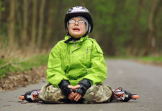 Boy fall on roller skates. Boy learns to skate on inline skates Stock Images