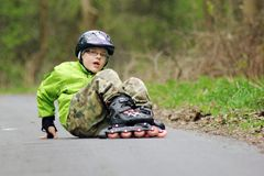 Boy fall on the skates. Boy learns to skate on inline skates Stock Photos
