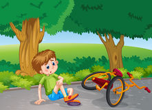 Boy falling down from bike in the park Stock Images