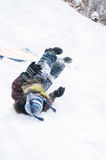 Boy falling off of toboggan Stock Images