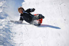 Boy Falling While Sledding Down the Hill. Boy falling while sledding fast down the hill with snow background Stock Photos