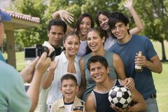 Boy (13-15) with family and friends posing for video camera. Royalty Free Stock Images