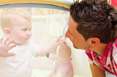 Boy and father. Baby boy in playpen looking at his father through mesh royalty free stock photo