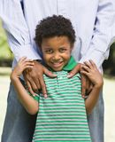 Boy and father. Smiling boy standing in front of father with his hands on shoulders royalty free stock images
