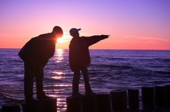 Boy with father. Boy pointing somewhere on the sea royalty free stock images