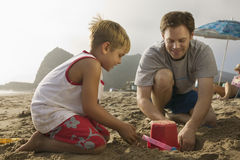Boy And Father Building Sand Castle At Beach Stock Photography