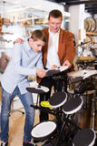Boy and father choosing best drum. Attractive teenage boy and smiling father choosing best drum unit in musical shop Stock Image