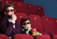 A boy with father at the cinema. A boy with father eating popcorn in 3D movie theater royalty free stock photography