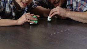 Boy and father competing in toy cars racing on the floor at home, playing game. Stock footage stock video footage