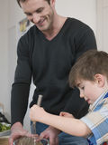Boy And Father Cooking Food In Kitchen Royalty Free Stock Images