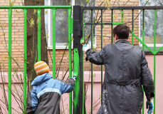 Boy and father, they dye fence by green color Royalty Free Stock Photos