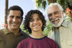 Boy (13-15) with Father and Grandfather outdoors front view portrait. royalty free stock photography