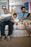 Boy with father and grandfather sitting on sofa. In living room at home Royalty Free Stock Photos