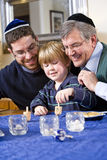Boy with father and grandfather spinning dreidel. Celebrating Hanukkah