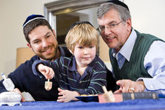 Boy with father and grandfather spinning dreidel royalty free stock photo