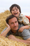 The boy and father on hay Royalty Free Stock Image