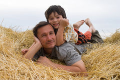 The boy and father on hay royalty free stock images