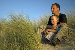Boy With Father Looking. A boy and his father are looking far away, to the horizon. They are sitting in the dunes Stock Photo
