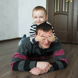Boy father lying on the floor at home Stock Photography