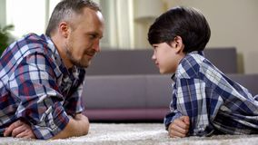 Boy and father lying on floor and looking at each other, making contact with kid stock photo