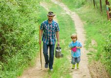 Boy and father in nature with watering can and shovel. Dad teaching son care plants. Arbor day. Planting trees. Tree. Planting tradition. Little helper in royalty free stock image