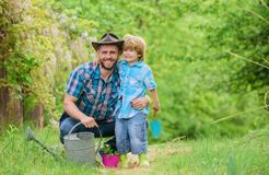 Boy and father in nature with watering can. Spring garden. Dad teaching little son care plants. Little helper in garden royalty free stock photos