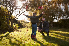 Boy And Father Playing With Autumn Leaves in Garden Royalty Free Stock Images