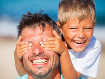 Boy with father playing at the beach. Little boy covers his dads eyes while playing at the beach stock photography