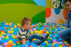A boy with father in the playing room with many little colored balls Stock Images