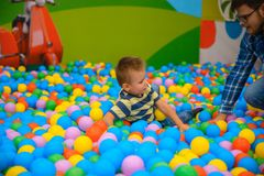 A boy with father in the playing room with many little colored balls Stock Photo