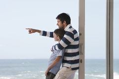 Boy With Father Pointing Out To Sea Stock Photo
