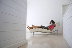 Boy With Father Reclining On Lounge Chair Stock Photography