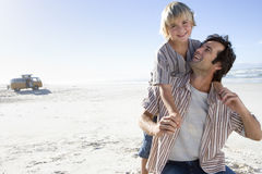 Boy (6-8) on father`s back on beach, smiling, portrait of boy Stock Photography