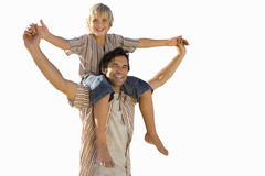 Boy on father's shoulders holding hands, smiling, portrait, cut out royalty free stock images